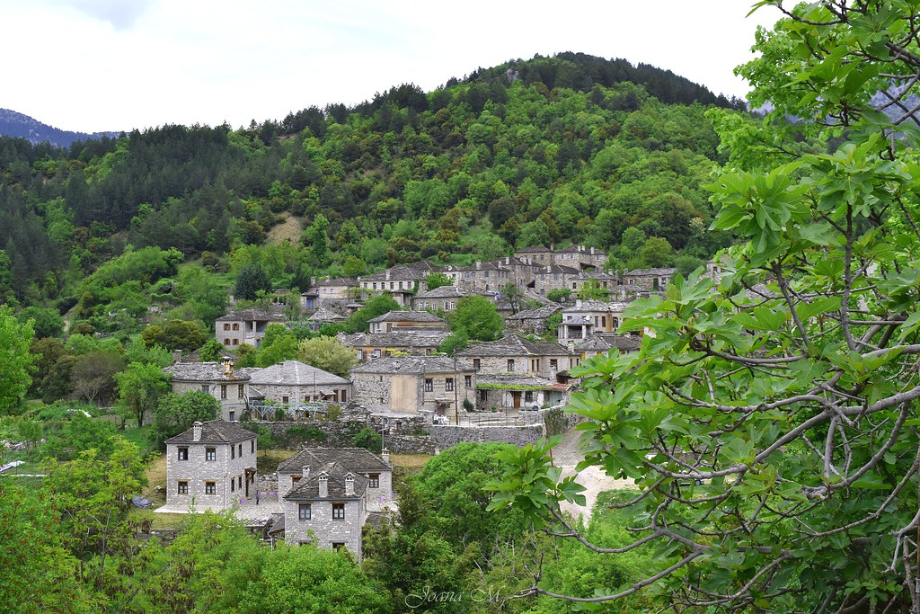 photo of a village of stone huts nestled in a lush green valley