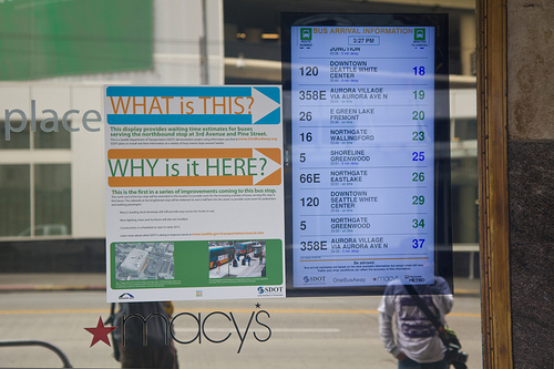 Large TV display in a store showing OneBusAway real-time arrival info