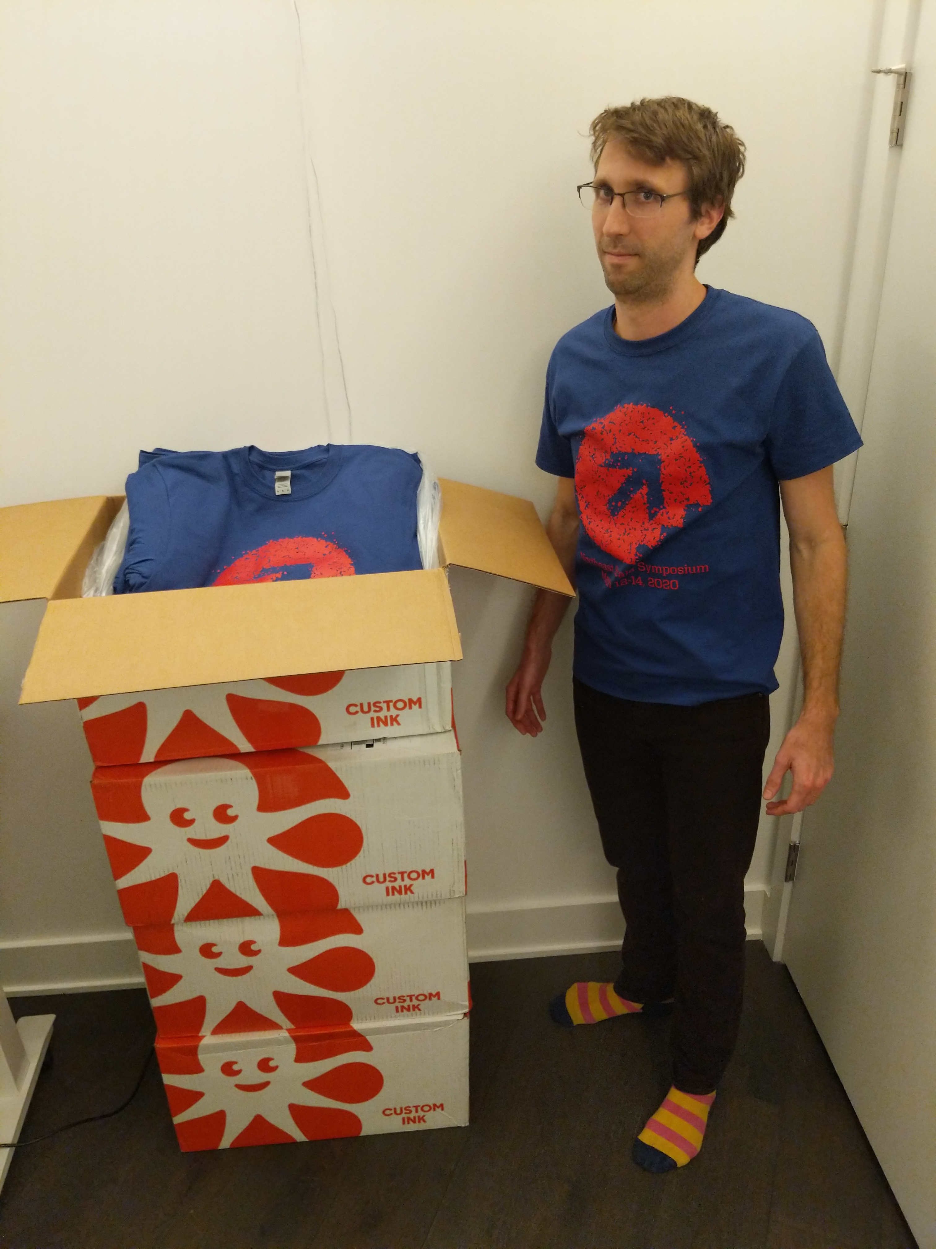 Ryan standing next to a large stack of boxes full of t-shirts
