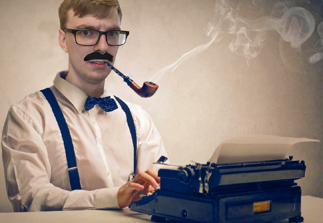 Picture of Brad Parbs sitting behind typewriter, smoking a pipe.
