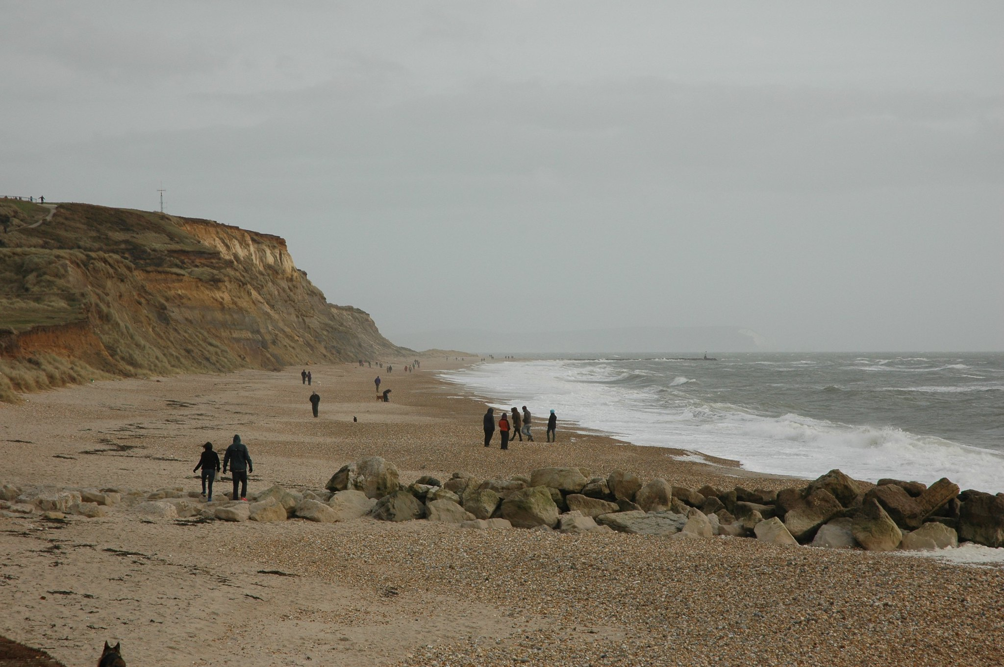 People on the beach with a clifftop